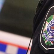 Queensland police officer's badge next to a police car