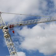 Construction cranes on a building site with clouds behind