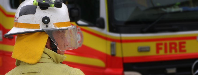 Queensland fire and emergency services Firefighter Brenton Mazey next to a fire engine
