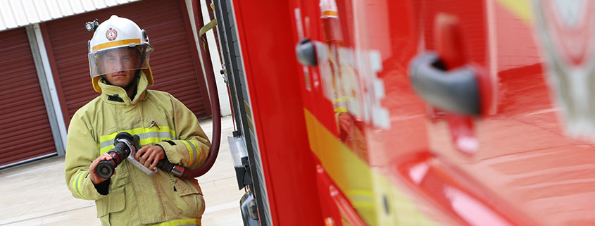 Queensland fire and emergency services firefighter holding a fire hose
