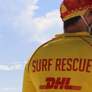 A Surf Rescue Patrol Officer in front of the red flags