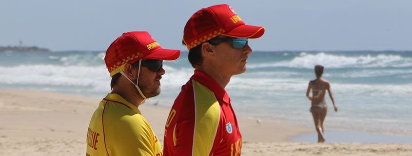 Two surf life savers and a swimmer at Main Beach on the Gold Coast