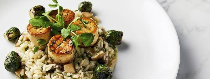 This image released by the Golden Globe Awards shows a dish of king oyster mushroom scallops on a bed of wild mushroom risotto with roasted Brussels sprouts, prepared by Beverly Hilton Executive Chef Matthew Morgan. (Leslie Grow/Golden Globe Awards via AP)